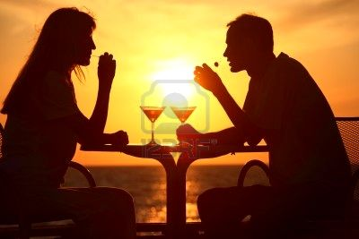 7792028-female-and-man-s-silhouettes-on-sunset-sit-at-table-with-two-glasses-and-olives-outdoor